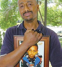 Luleseged Bete holds a picture Wednesday of his nine-year-old son, Sami, who fell from a 28th-floor balcony.