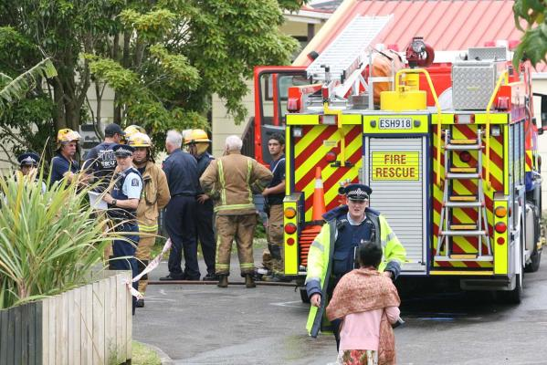 A police officer speaks with a woman as emergency services investigate a west Auckland house fire