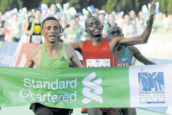 Dejere Abera of Ethiopia (left) beats Kenyans Cosmas Kyeva (centre) and Julius Maisei at the finish line to win the Standard Chartered Hong Kong Marathon on February 5, 2012