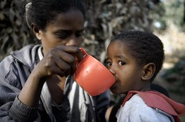 At Ethiopia's Entoto Mountain, a mother gives her HIV-positive son what local priests say is holy water.