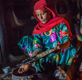 A villager preparing coffee beans for roasting