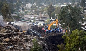 Police and rescue workers watch as excavators dig in search of missing people at the Reppi rubbish dump in Addis Ababa
