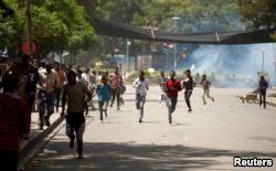 Protesters run from tear gas being fired by police during Irreecha, the thanks giving festival of the Oromo people in Bishoftu town of Oromia region, Ethiopia, October 2, 2016