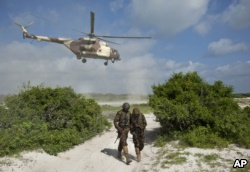 FILE - Two Kenyan army soldiers shield themselves from the downdraft of a Kenyan air force helicopter near the seaside town of Bur Garbo, Somalia, Dec. 14, 2011. A Kenyan military spokesman is categorically denying accusations that the Kenyan air force has been conducting airstrikes against Somali civilians.