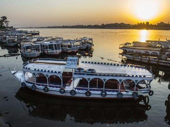 River boats are moored in the Nile at a marina at sunrise
