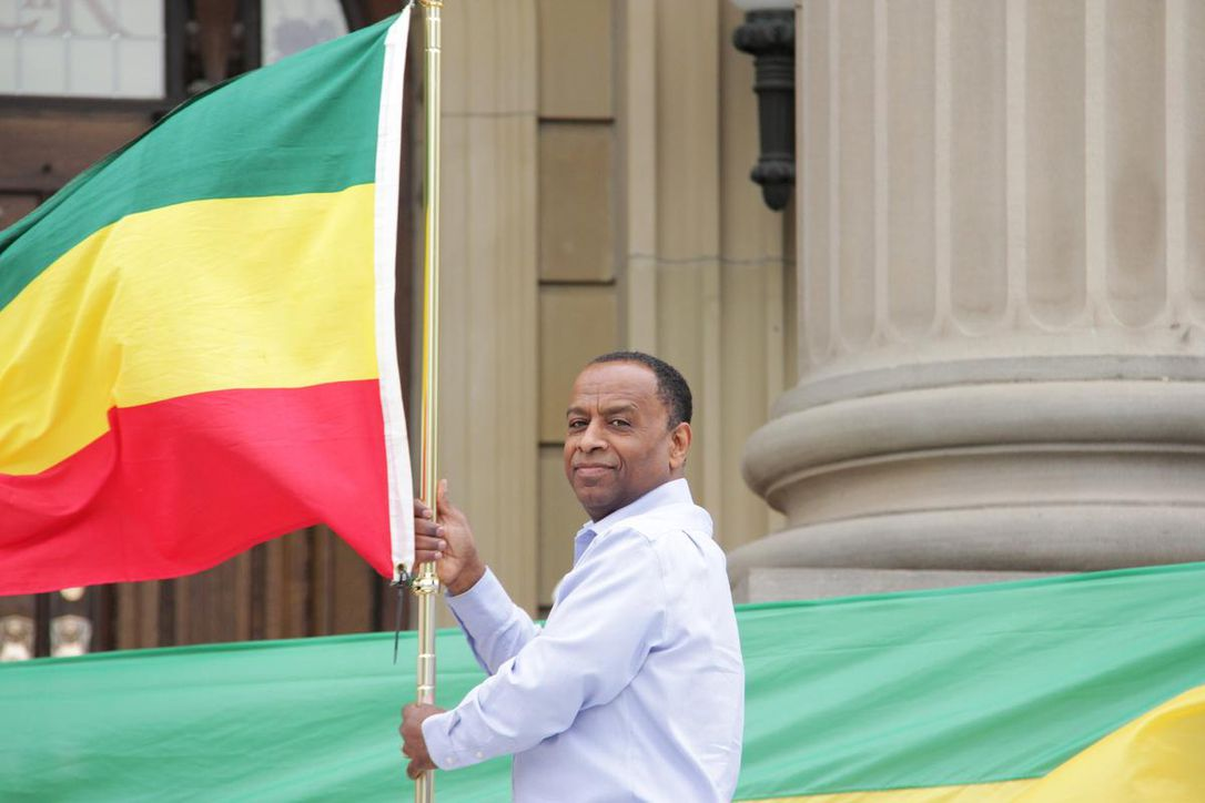 Beneyam Zeleke adjusts the Ethiopian flag at the Alberta legislature steps on Monday.