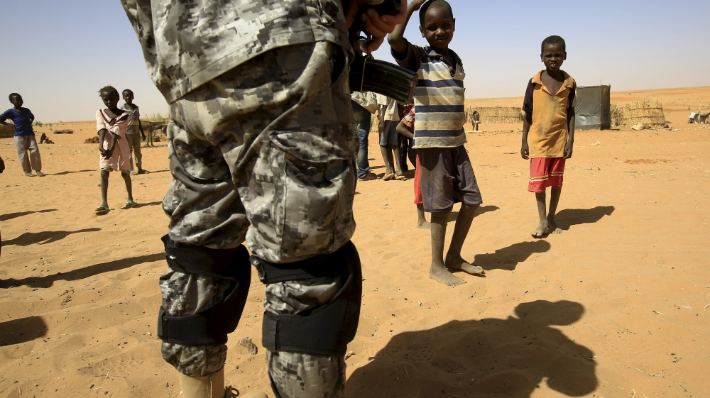 Newly arrived children look towards a UNIMED peacekeeper at the Zam Zam IDP camp, near Al Fashir in North Darfur