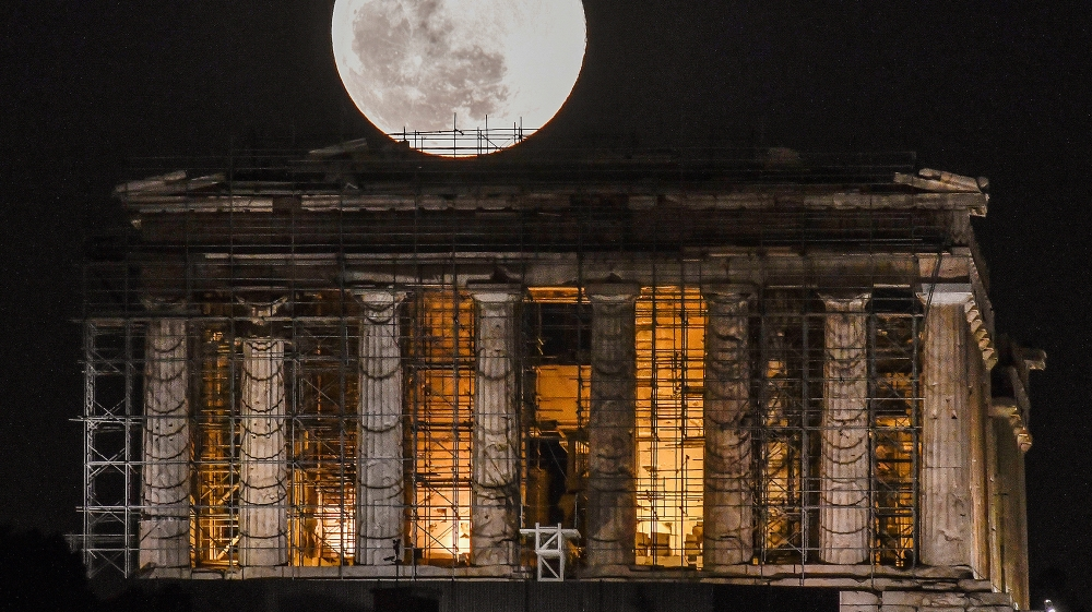 A full moon rises above Greek Parthenon Temple (438 BC), covered by scaffolding, at the Acropolis archaeological site in Athens on February 9, 2020 .  LOUISA GOULIAMAKI / AFP