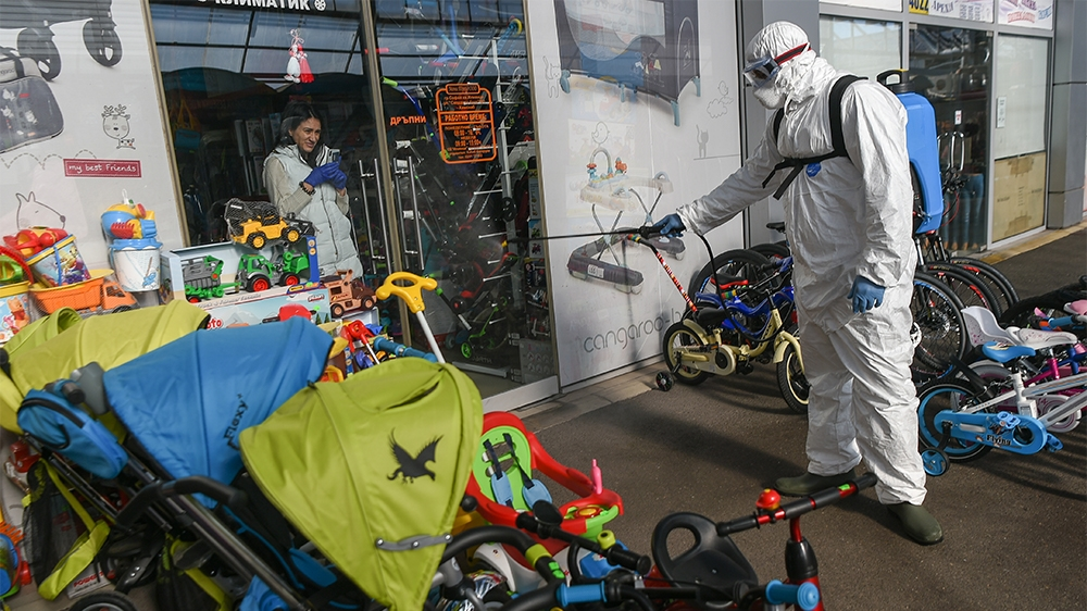 A store vendor takes photos of a member of Sofia's Municipality disinfecting the outside of her store in the biggest market for Chinese goods in Sofia, Bulgaria to prevent the spread of the COVID-19,
