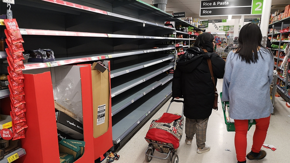 Consumers shop in near empty aisles of a supermarket in London on March 13, 2020, as consumers worry about product shortages, leading to the stockpiling of household products due to the outbreak of th