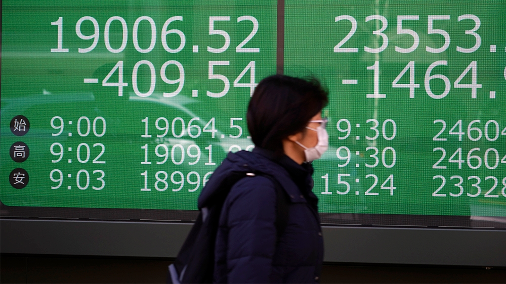 A woman walks past an electronic stock board showing Japan's Nikkei 225 and New York Dow index at a securities firm in Tokyo Thursday, March 12, 2020. (AP Photo/Eugene Hoshiko)