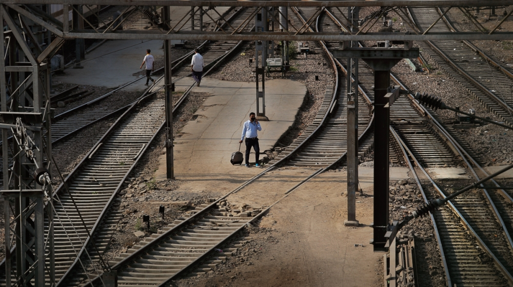 In this Monday, March 23, 2020, photo, a passenger walks past railway tracks at the deserted New Delhi Railway station during a lockdown amid concerns over the spread of Coronavirus, in New Delhi, Ind