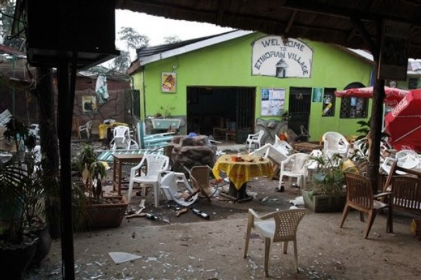 """Damaged chairs and tables amongst the debris strewn outside the restaurant """"Ethiopian village"""" in Kampala, Uganda, Monday, July 12, 2010 after an explosion at the restaurant late Sunday."""