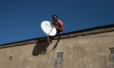 man-sets-up-sattelite-dish-in-Zimbabwe