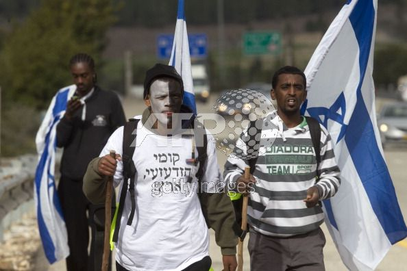 Molat Araro (C), 26, an Israeli Jew of Ethiopian origin with his face painted black and white, walks with others on a highway in Latrun to Jerusalem as they protest against racism on January 17, 2012. Thousands of Israeli Ethiopian Jews will protest on January 18 against racism in Jerusalem. AFP PHOTO/MENAHEM KAHANA (Photo credit should read MENAHEM KAHANA/AFP/Getty Images)
