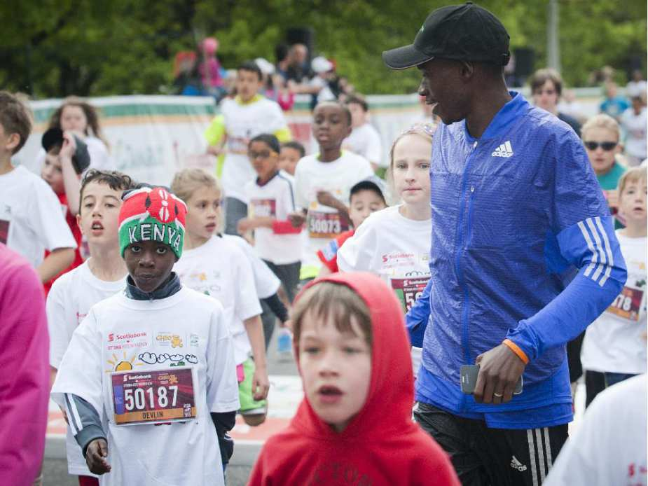 Devlin Taillon, 8, with Kenyan mentor David Kogei, who finished the 10K yesterday in third place at the end of the kids marathon at Tamarack Ottawa Race Weekend, Sunday, May 24, 2015.
