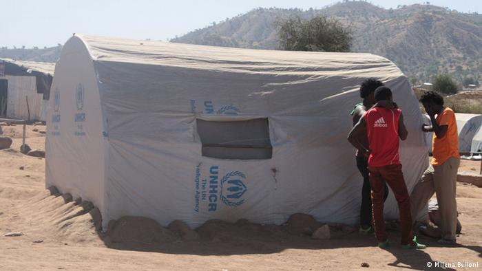 Three men stand in a narrow strip of shade provided by a refugee tent. Photo: Copyright: Milena Belloni
