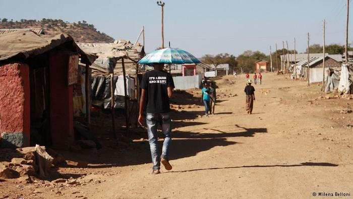 A man carrying an umbrella to protect against the sun walks down a street in the Adi Harush refugee camp. Photo: Copyright: Milena Belloni