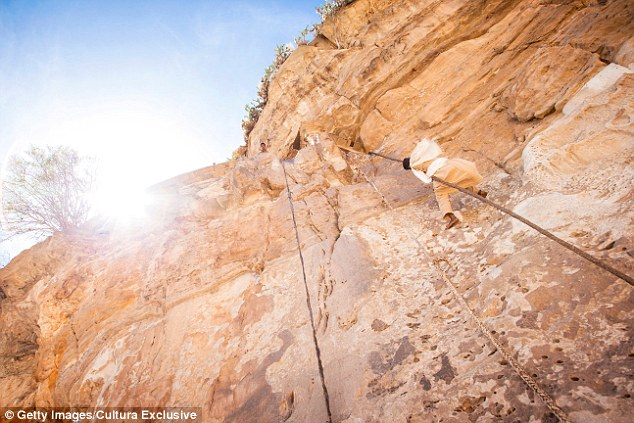 A priest climbs a rope to the 6th century monastery, Debre Damo,  west of Adigrat in the Tigray Region