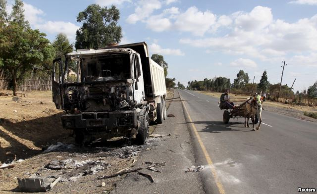 FILE - A man drives a horse-cart past the wreckage of a truck torched during demonstrations along the road in Holonkomi town, in Oromia region of Ethiopia, Dec. 17, 2015.