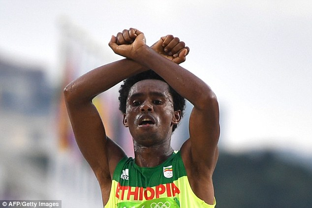 Ethiopian marathon runnerFeyisa Lilesa (pictured as he finishes the marathon in Rio on Sunday) crossed his arms above his head, in an act of defiance against his government