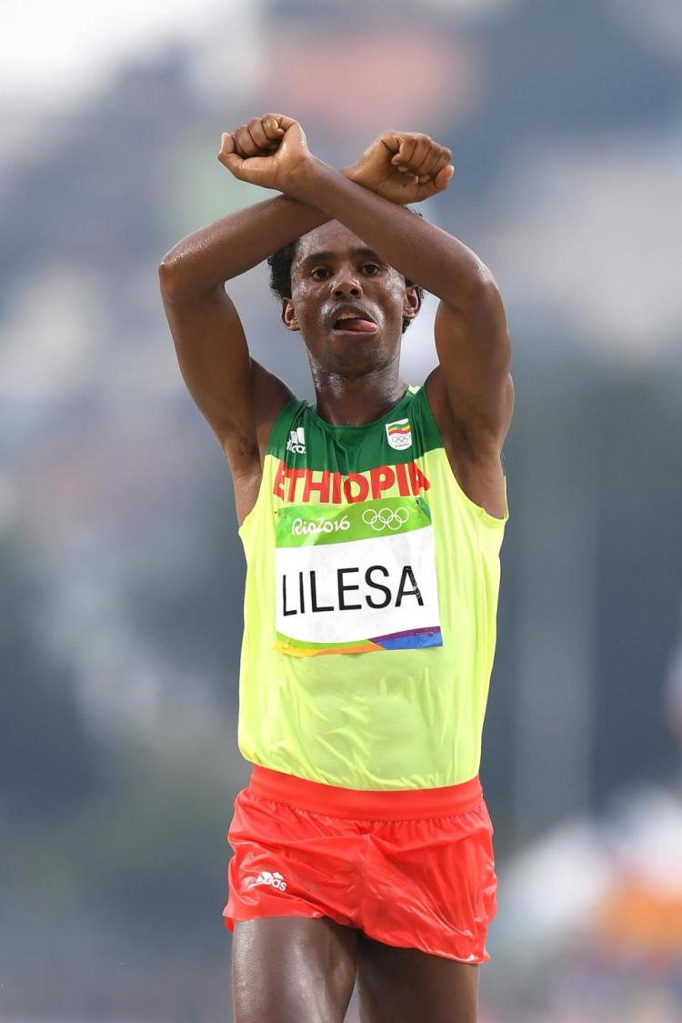 Feyisa Lilesa of Ethiopia celebrates as he crosses the line to win silver during the marathon in Rio.
