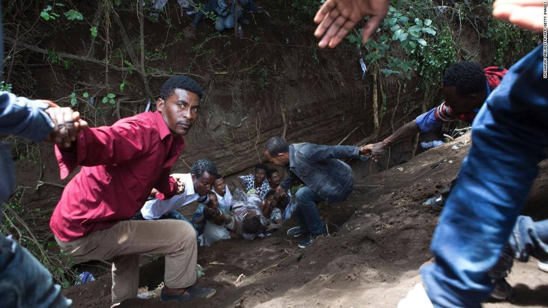 Bystanders work to remove an injured man from a ditch.