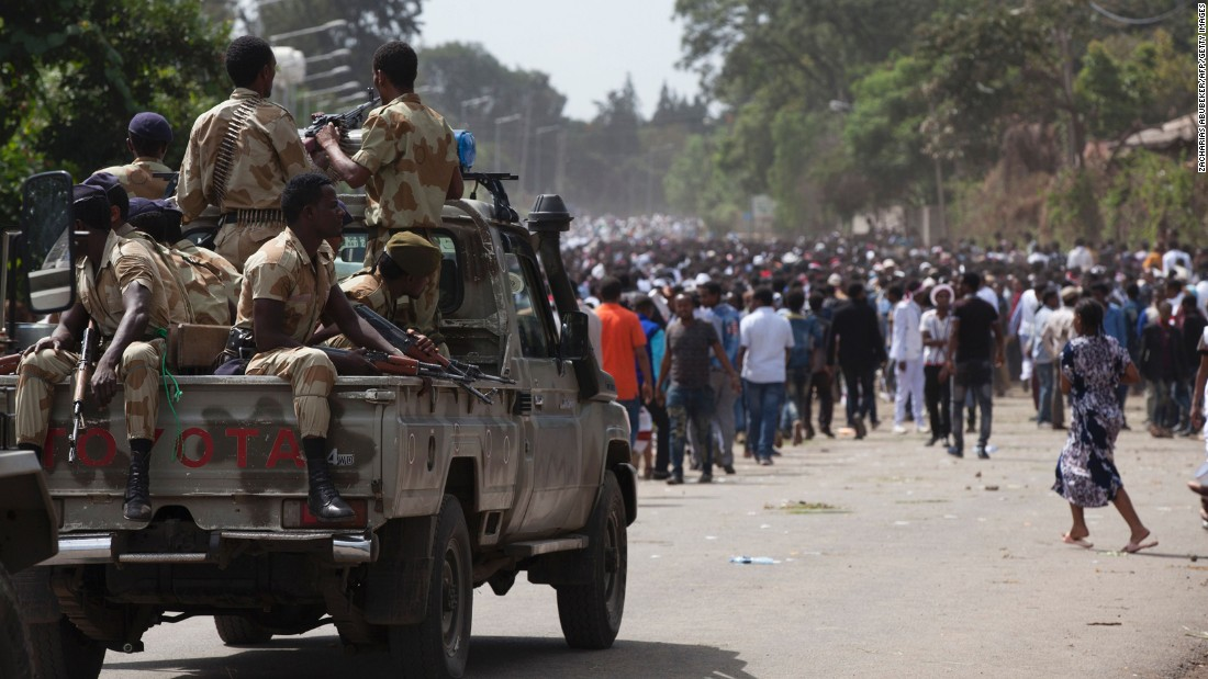 Oromo regional police officers wait in a pickup near a crowd of festival attendees.