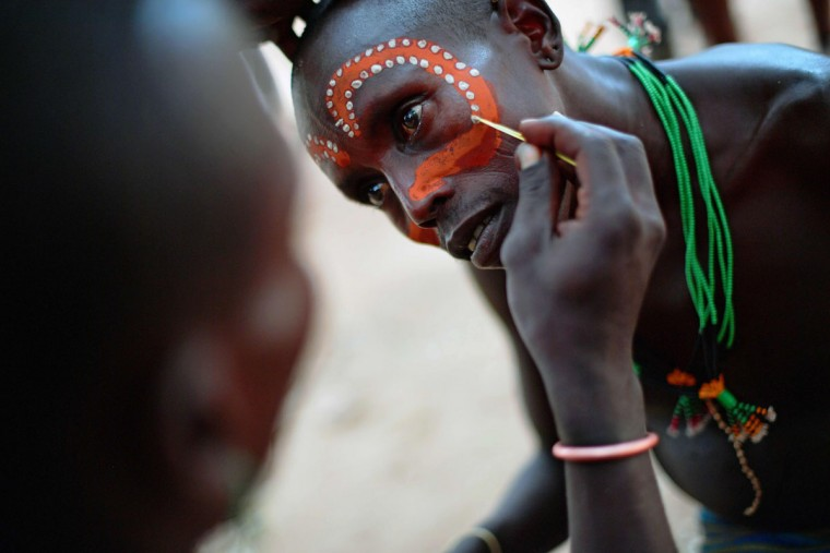 "A Hamar man has his face painted before a bull jumping ceremony in Ethiopia's southern Omo Valley region near Turmi on September 19, 2016. The Hamar are a Nilotic ethnic group in Ethiopia. Bull jumping has been practised by the Hamars for thousands of years. The ceremony is a coming of age tradition which allows young men to marry. The man has to run across the backs of bulls which have been lined up, 4 times. If he falls through the row of bulls he is to start again until he finishes without falling. If the man fails to properly ""jump the bulls"" he risks humiliation and being cast out by his village as well as never being able to marry in the future. Before the ceremony women line up to be whipped by men holding sticks to prove their devotion to the men. The construction of the Gibe III dam, the third largest hydroelectric plant in Africa, and large areas of very ""thirsty"" cotton and sugar plantations and factories along the Omo river are impacting heavily on the lives of tribes living in the Omo Valley who depend on the river for their survival and way of life. Human rights groups fear for the future of the tribes if they are forced to scatter, give up traditional ways through loss of land or ability to keep cattle as globalisation and development increases. (AFP PHOTO / CARL DE SOUZA)"