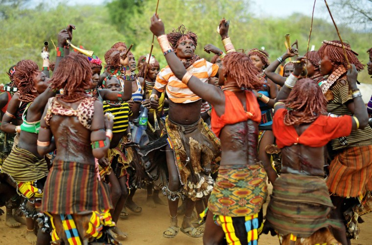 "Hamar women dance before a bull jumping ceremony in Ethiopia's southern Omo Valley region near Turmi on September 19, 2016. The Hamar are a Nilotic ethnic group in Ethiopia. The construction of the Gibe III dam, the third largest hydroelectric plant in Africa, and large areas of very ""thirsty"" cotton and sugar plantations and factories along the Omo river are impacting heavily on the lives of tribes living in the Omo Valley who depend on the river for their survival and way of life. Human rights groups fear for the future of the tribes if they are forced to scatter, give up traditional ways through loss of land or ability to keep cattle as globalisation and development increases. (AFP PHOTO / CARL DE SOUZA)"