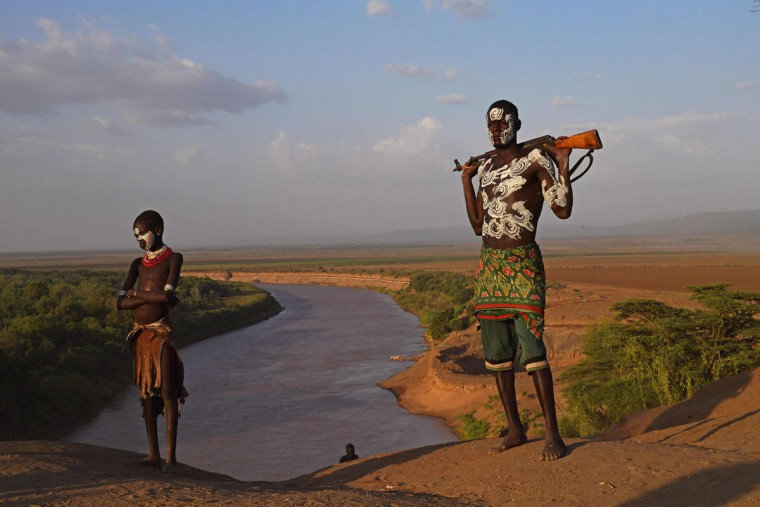 "Members from the Karo tribe pose in front of the Omo river in Ethiopia's southern Omo Valley region on September 23, 2016. The Karo are a Nilotic ethnic group in Ethiopia famous for their body painting. They are also one of the smallest tribes in the region. The construction of the Gibe III dam, the third largest hydroelectric plant in Africa, and large areas of very ""thirsty"" cotton and sugar plantations and factories along the Omo river are impacting heavily on the lives of tribes living in the Omo Valley who depend on the river for their survival and way of life. Human rights groups fear for the future of the tribes if they are forced to scatter, give up traditional ways through loss of land or ability to keep cattle as globalisation and development increases. (AFP PHOTO / CARL DE SOUZA)"