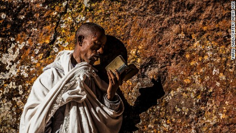 A pilgrim reading a bible and pressing his cheek to the holy walls of a church at Lalibela.