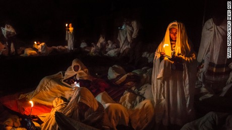 A group of pilgrims pray and read their bibles by candlelight around the churches of Lalibela.