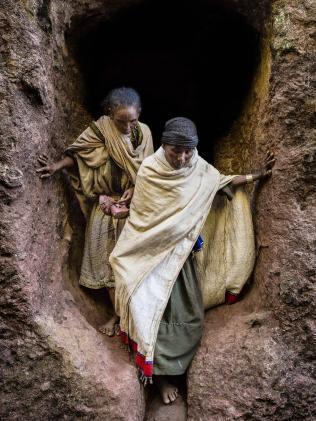 Two pilgrims navigate the tunnels.