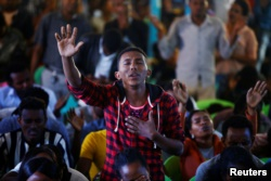 A man attends a prayer session at Biftu Bole Lutheran Church during a prayer and candle ceremony for protesters who died in the town of Bishoftu, in Addis Ababa, Ethiopia, Oct. 16, 2016.