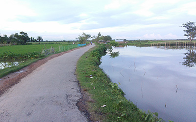 Rural road dividing high and low water in Bangladesh