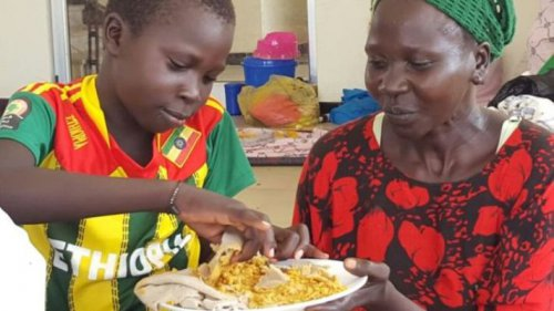 Ethiopian Nuer child, Jany, eating with his mother after he was rescued from Murle abductors (BBC photo)