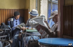 Ethiopian men read newspapers at a cafe in Addis Ababa, Ethiopia on Oct. 10, 2016. Ethiopia's government on Monday blamed Egypt for supporting outlawed rebels and forcing the declaration of the country's first state of emergency in a quarter-century as widespread anti-government protests continue.