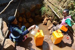 Women collect water from a muddy well in Sululta town in Ethiopia