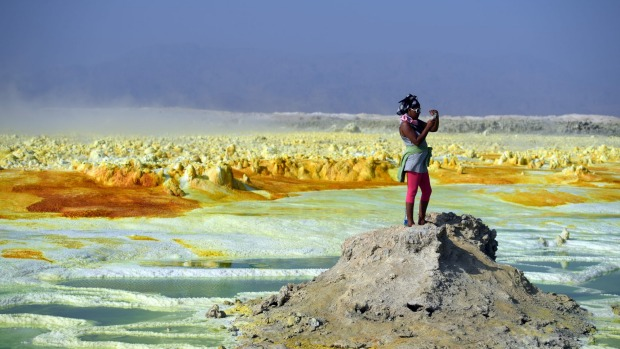 A tourist take a photograph of a sulphur lake in the Danakil Depression. The landscape is quite alien-like.