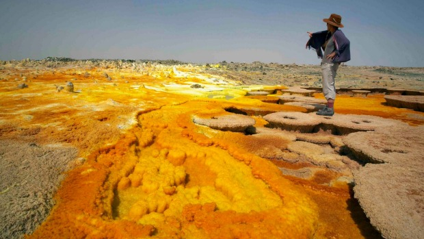 A tourist walks along sulphur and mineral salt formations created by the upwelling springs of Dallol volcano.