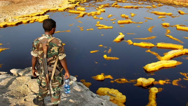 A soldier, part of an escort group, looks over the brightly coloured sulfur springs in Ethiopia's Afar Region.