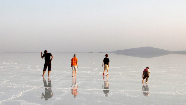 Travellers in the author's party admire their reflections in the massive salt flats of the Afar Region.