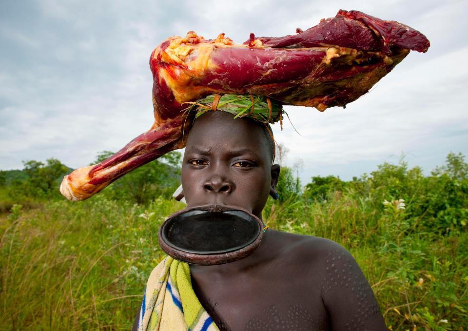 A tribeswoman sporting a huge lip plate and wearing a skinned animal carcass on her head