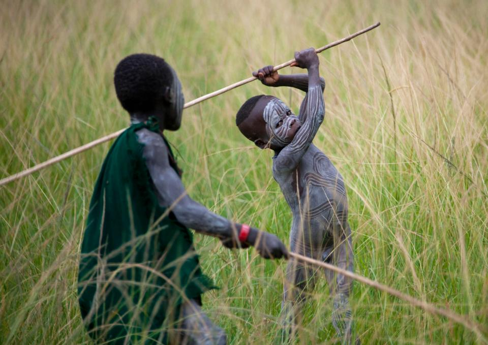 Children of a very young age are seen copying the warriors in dress and wielding the stick weapons