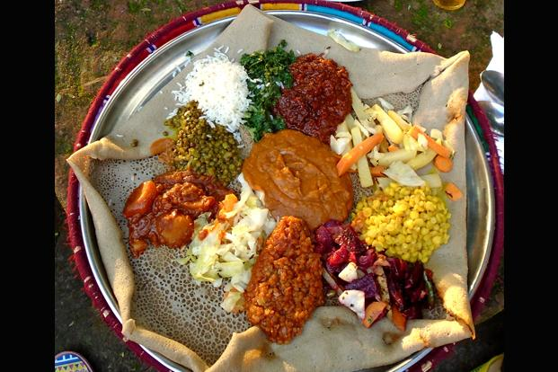 The injera was spread over a large plate, topped with portions of various dry and curry-like preparations.