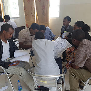 A group of men sitting around a table at a financial management course in Ethiopia.