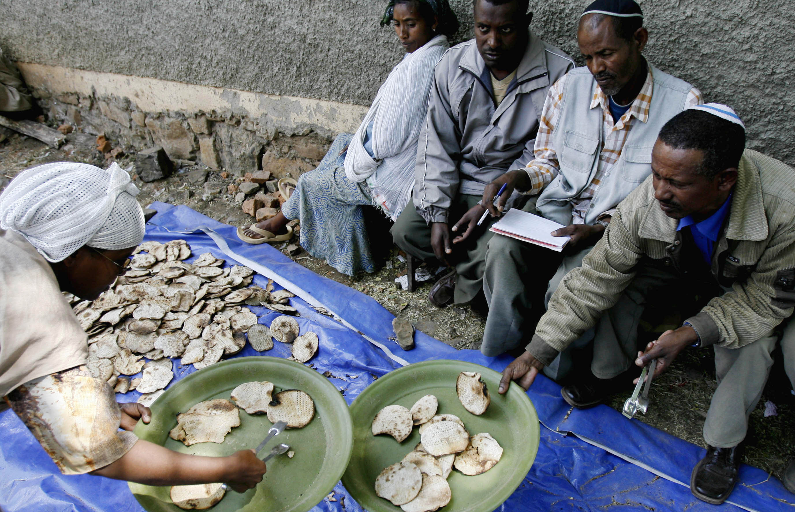 An Jewish Ethiopian woman gives matzahto a man ahead of Passover at a compound while awaiting immigration to Israel in Gondar March 9, 2007 (ELIANA APONTE/REUTERS).