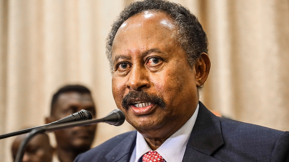 FILE - In this Wednesday, Aug. 21, 2019 file photo, Sudan's new Prime Minister Abdalla Hamdok speaks during a press conference in Khartoum, Sudan. Hamdok said in the interview that ending his country'