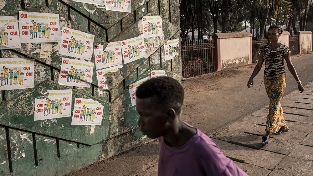 Guineans walk in front of posters advertising